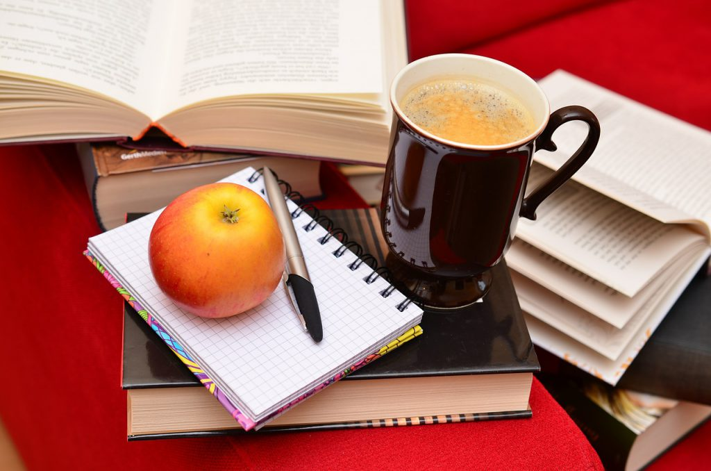 fall productivity: apple and coffee on stacked books
