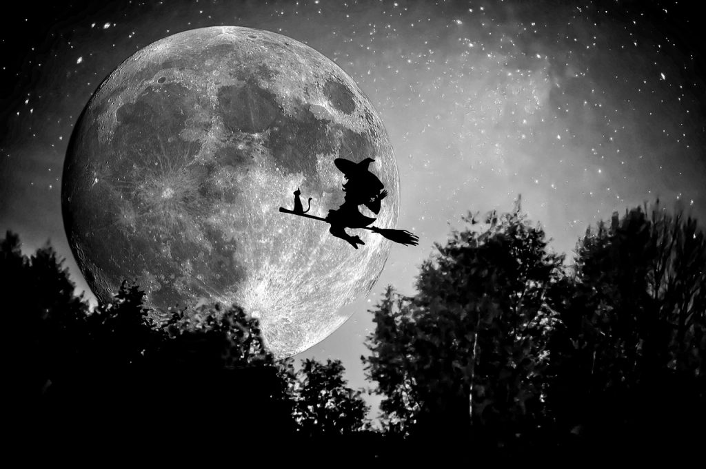 witch flies on broomstick across full moon to inspire creativity on November 1